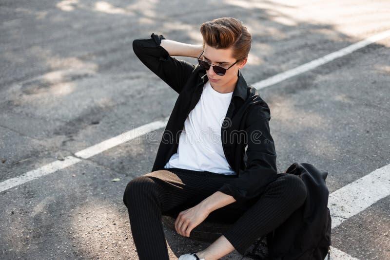 De Europese jonge mens met in kapsel in elegante kleren in zonnebril met een rugzak zit in openlucht op een rubberwiel royalty-vrije stock afbeeldingen