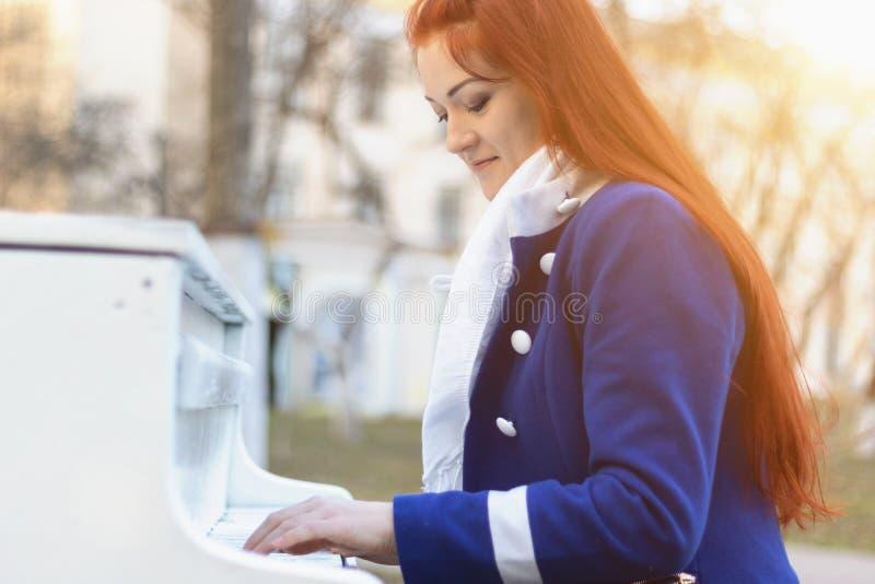 De Europese Kaukasische vrouwen met rood haar glimlacht en speelt de piano in het park bij zonsondergang De moderne en klassieke  stock fotografie