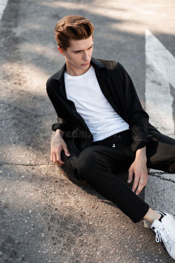 De Europese leuke jonge mens in een zwart modieus overhemd in een T-shirt in gestreepte zwarte broek in in tennisschoenen zit op  stock foto's
