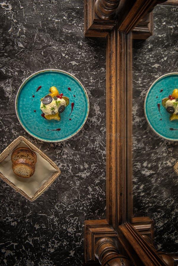 De exclusieve kaasmousse met gemarineerde okkernoten en gouden bieten diende op turkooise plaat, hoogste gastronomie royalty-vrije stock afbeeldingen