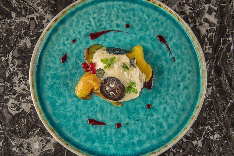 De exclusieve kaasmousse met gemarineerde okkernoten en gouden bieten diende op turkooise plaat, hoogste gastronomie stock afbeelding