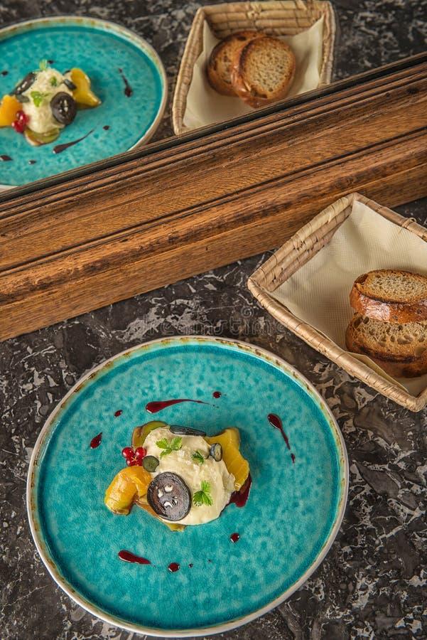De exclusieve kaasmousse met gemarineerde okkernoten en gouden bieten diende op turkooise plaat, hoogste gastronomie stock foto