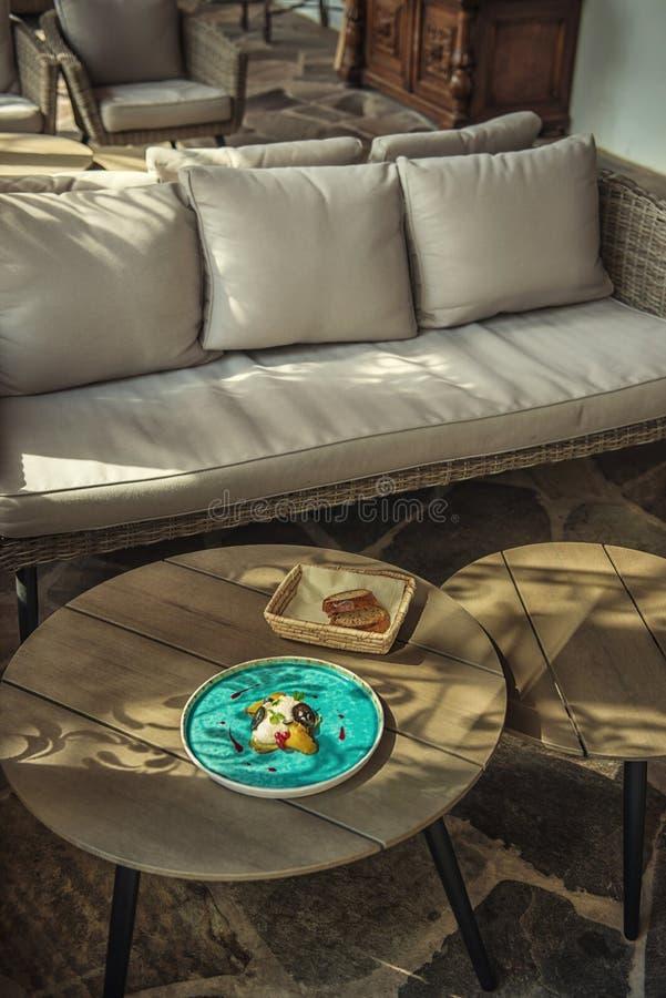 De exclusieve kaasmousse met gemarineerde okkernoten en gouden bieten diende op turkooise plaat, hoogste gastronomie stock afbeeldingen