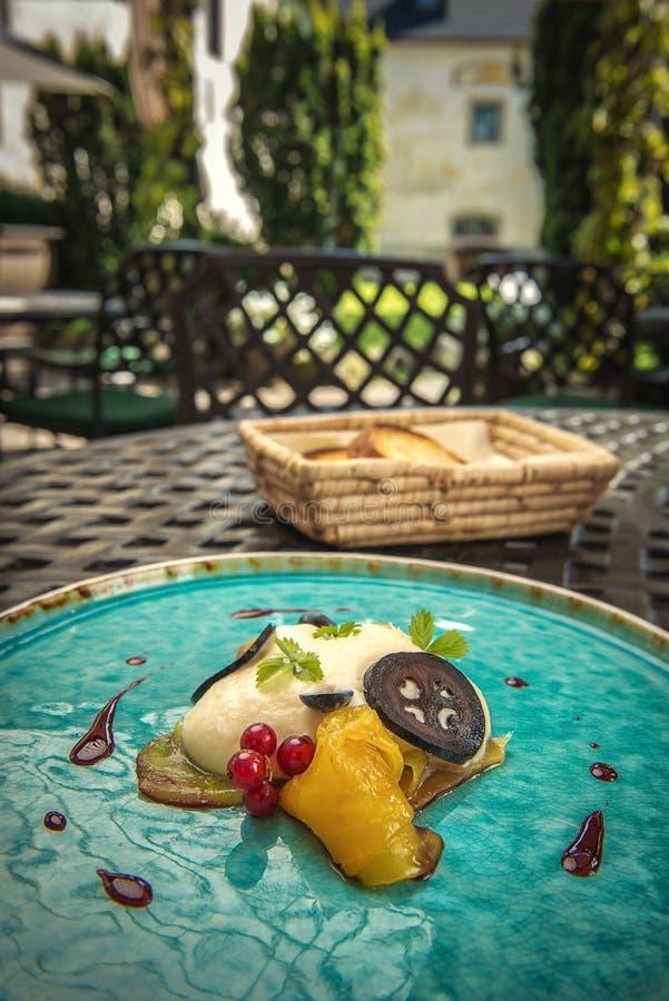 De exclusieve kaasmousse met gemarineerde okkernoten en gouden bieten diende op turkooise plaat, hoogste gastronomie royalty-vrije stock fotografie