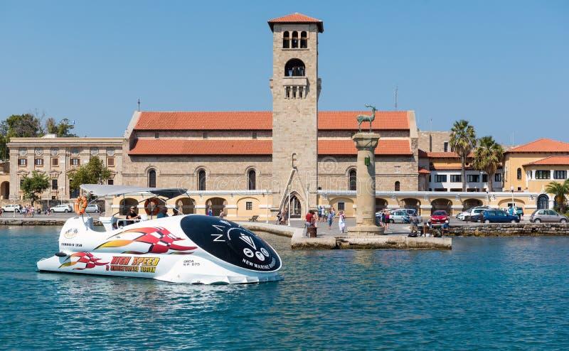 De excursieboot drijft langs oude Venetiaanse horlogetoren bij oude zeehaven van het eiland van Rhodos, Griekenland stock fotografie