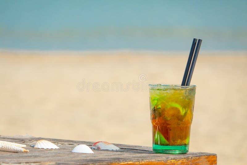 De exotische de zomerdrank, vertroebelt zandig strand op achtergrond Verse mojitococktail Gelukkig de zomer overzees vakantieconc stock foto's
