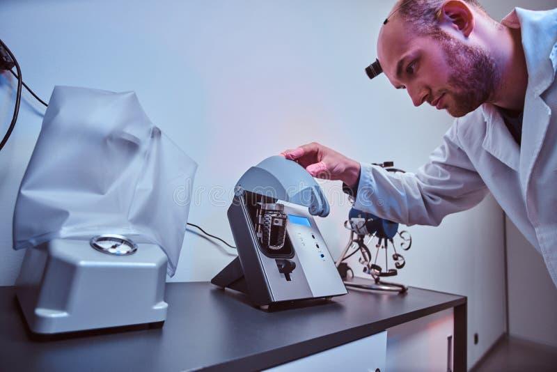 De Expiriencedhorlogemaker doet gravure voor het horloge van custmer gebruikend speciaal hulpmiddel op zijn workshop stock foto