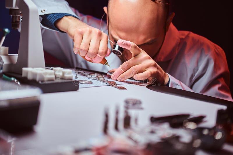 De Expiriencedhorlogemaker doet gravure voor het horloge van custmer op zijn workshop stock foto