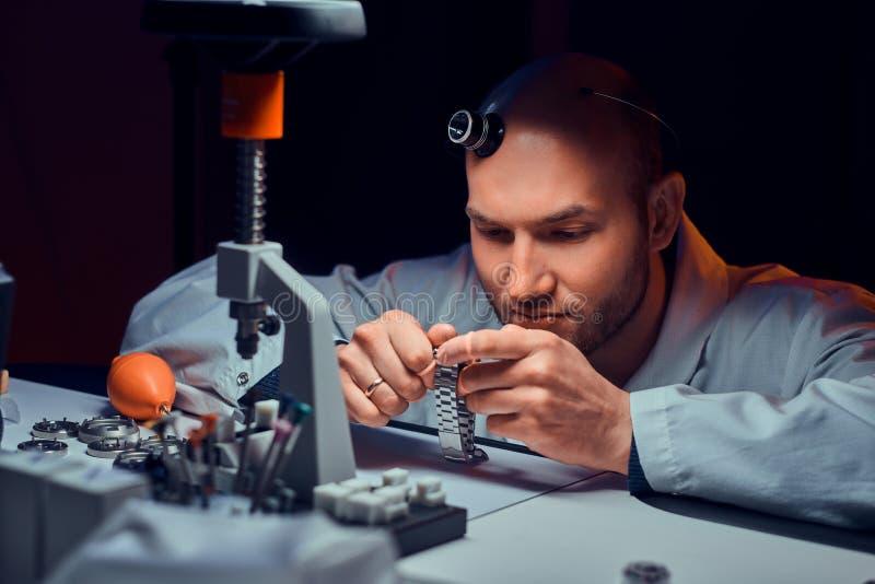 De Expiriencedhorlogemaker doet gravure voor het horloge van custmer op zijn workshop royalty-vrije stock foto's