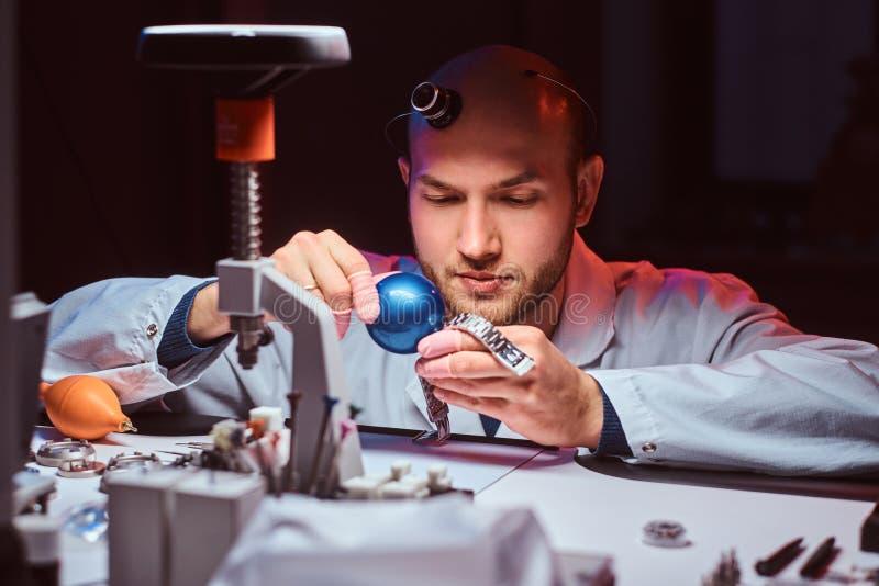 De Expiriencedhorlogemaker doet gravure voor het horloge van custmer op zijn workshop stock foto's