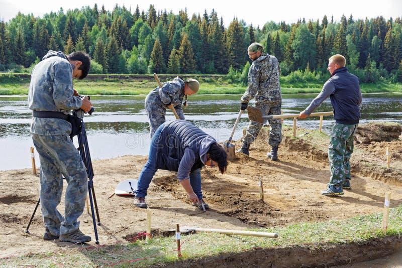 De exploitant neemt een video van een groep mensen die bij de archeologische uitgravingen aan de rivierbank werken stock fotografie