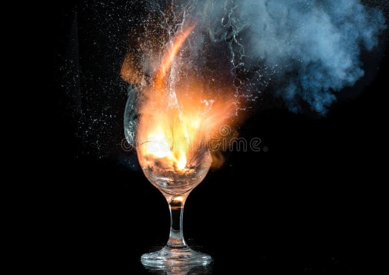 De explosie van wijn in een glas, heel wat plonsen en fragmenten, het kwaad van alcohol stock afbeeldingen