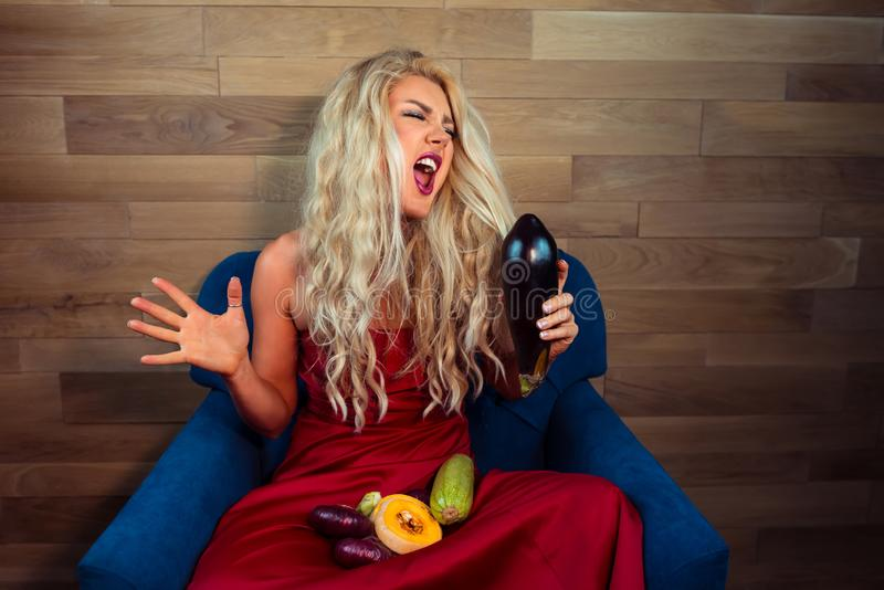 De expressieve vegetarische vrouw zit op leunstoel op achtergrond van houten muur stock foto's