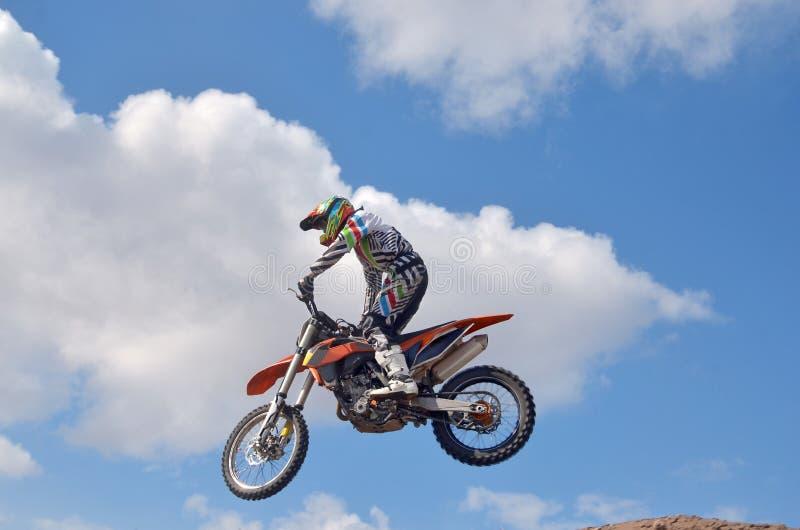 De Exstrimbestuurder die zich op de MX motorfiets bevinden vliegt over royalty-vrije stock afbeelding