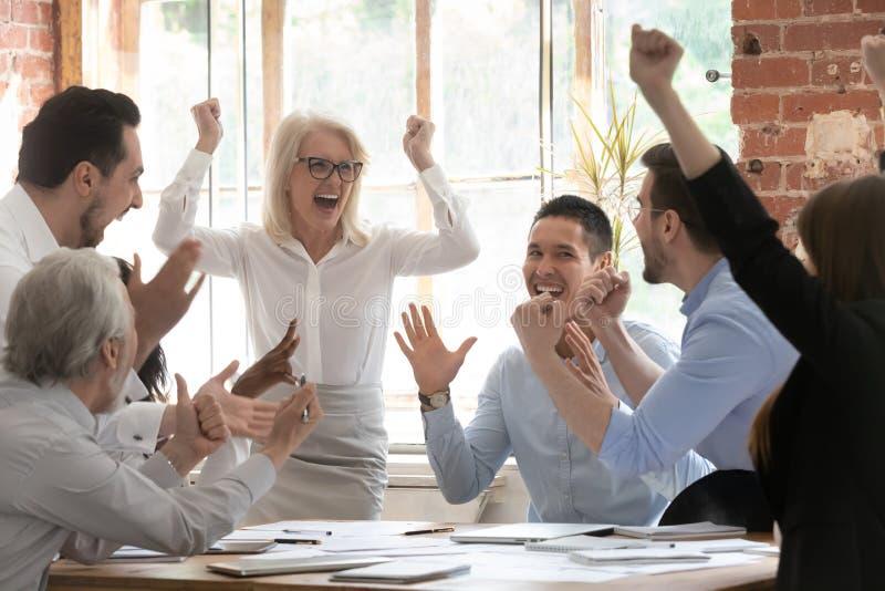De extatische gelukkige collectieve van commerciële schreeuw teammensen viert triomf royalty-vrije stock foto's