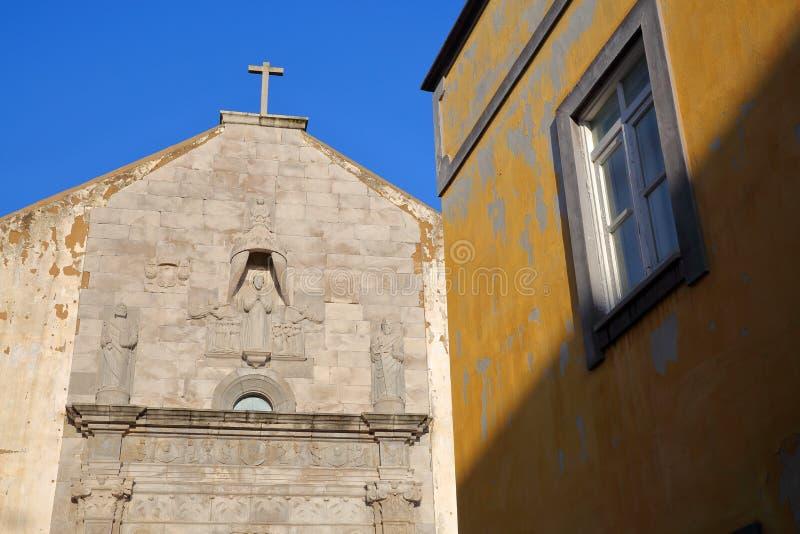 De externe voorgevel van Misericordia-kerk in Tavira, Algarve, met een kleurrijke voorgevel in de voorgrond stock afbeeldingen