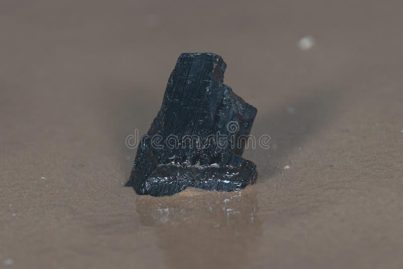 De extra brok van Rang Zwarte Tourmaline van Brazilië op nat zand op het strand voor het meer royalty-vrije stock foto