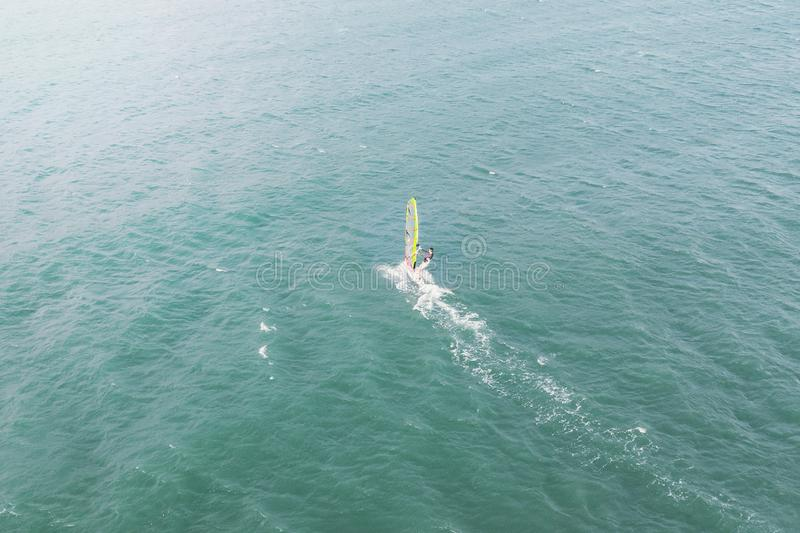de extreme mensenatleet zwemt op de windbranding op de overzeese golf tegen het blauwe overzees en de horizon Extreme watersporte stock foto's