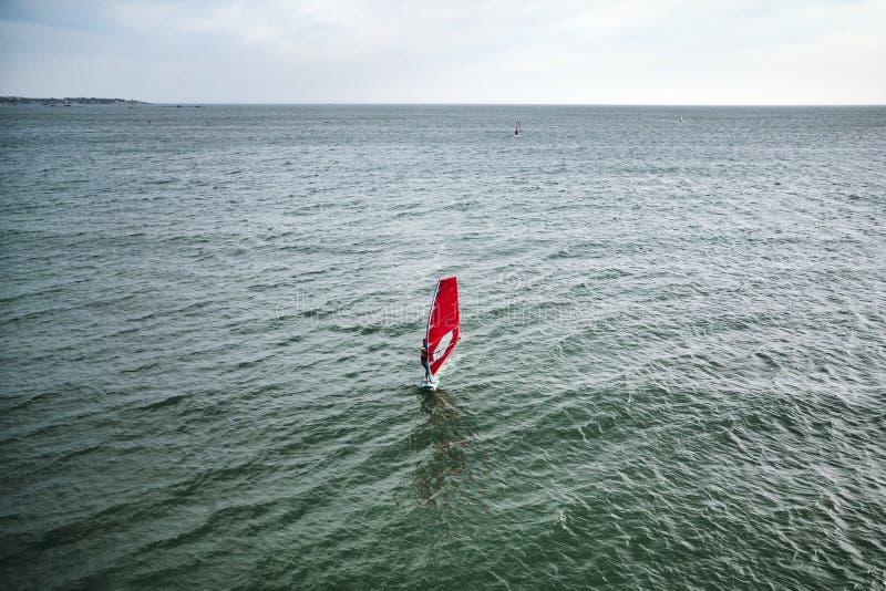 de extreme mensenatleet zwemt op de windbranding op de overzeese golf tegen het blauwe overzees en de horizon Extreme watersporte stock afbeelding
