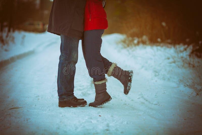 De förälskade omfamningarna för par utomhus i vinter fotografering för bildbyråer