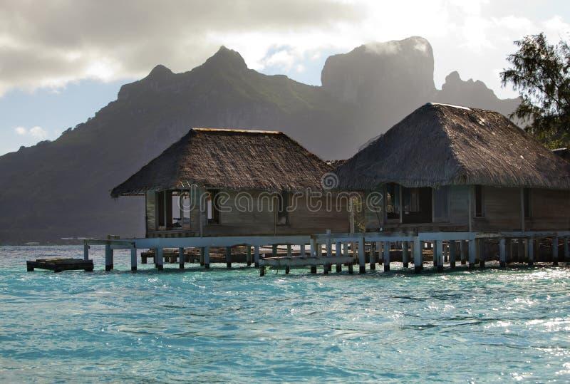 De förstörda kastade kojorna på vatten och ön med palmträd i havet och bergen på en bakgrund royaltyfria bilder