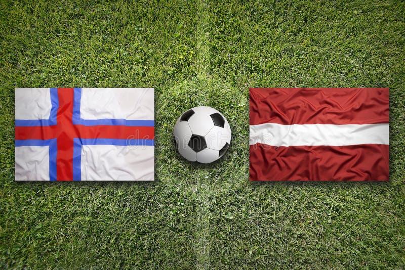 De Faeröer versus De vlaggen van Letland op voetbalgebied stock afbeelding