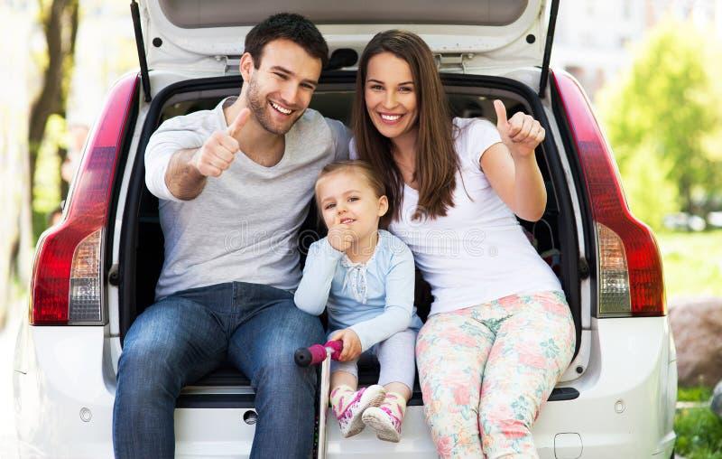 De familie in auto het tonen beduimelt omhoog