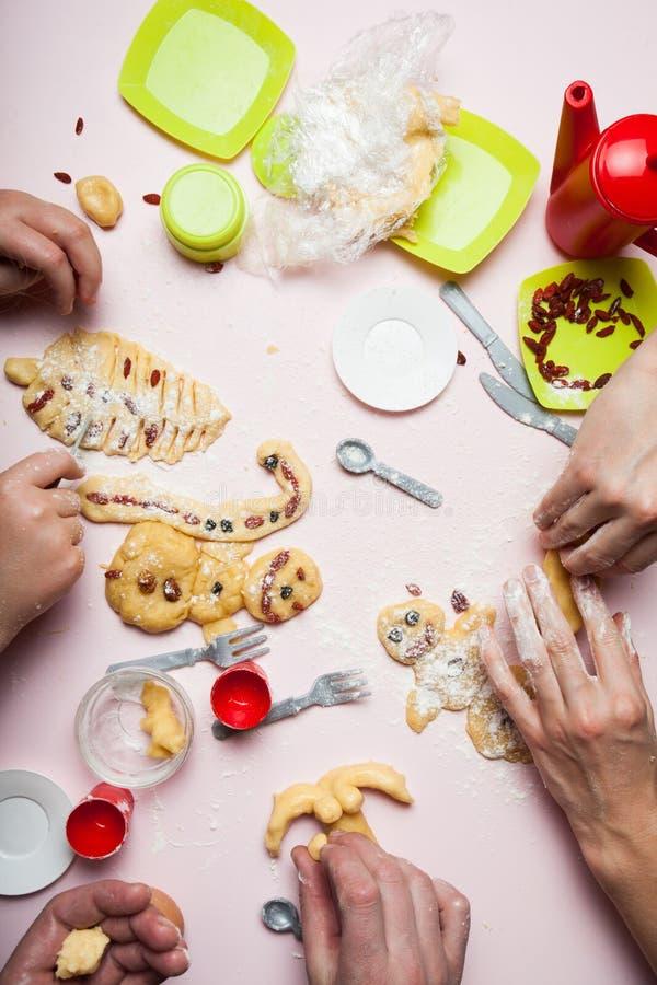 De familie bereidt Kerstmiskoekjes in de vorm van sneeuwmannen en een Kerstboom met droge bessen voor stock foto's