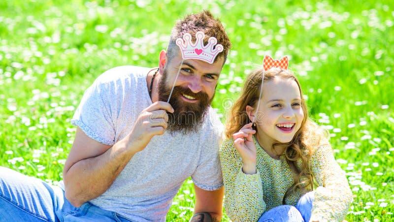 De familie besteedt vrije tijd in openlucht, speelt meisjesachtige spelen Kind en vader het stellen met kroon en boog de attribut royalty-vrije stock afbeeldingen