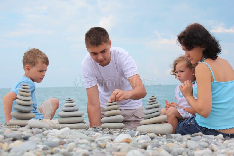 De familie bouwt steenstapels op kiezelsteenstrand stock afbeeldingen