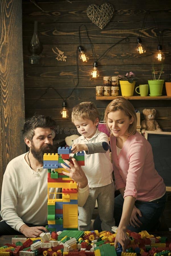 De familie brengt samen tijd in speelkamer door De ouders helpen leuke zoon om een huis uit plastic blokken te maken Papa het ste stock afbeelding