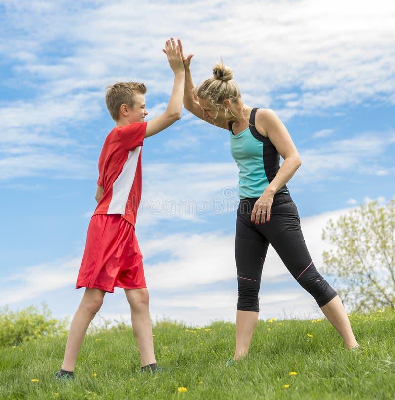 De familie, de moeder en de zoon lopen in openlucht of stoten voor sport aan royalty-vrije stock fotografie