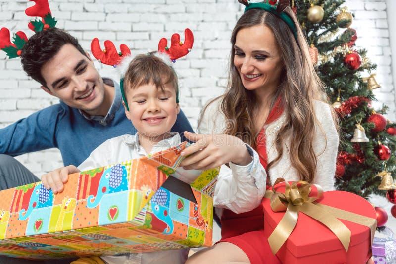 De familie die kleurrijke Kerstmis openen stelt voor royalty-vrije stock afbeelding