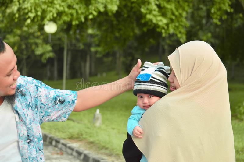 De familie die van gelukkige moslim bij openluchtpark lopen die een baby in dagtijd houden stock foto's