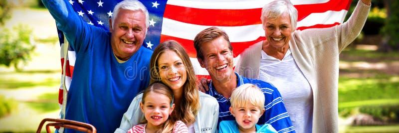De familie die van meerdere generaties Amerikaanse vlag in het park houden royalty-vrije stock afbeeldingen