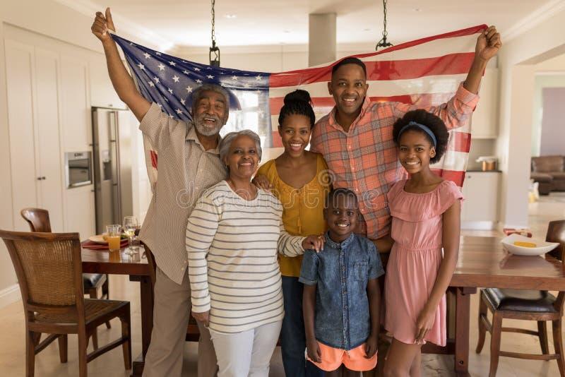 De familie die van meerdere generaties een Amerikaanse vlag thuis houden stock foto's
