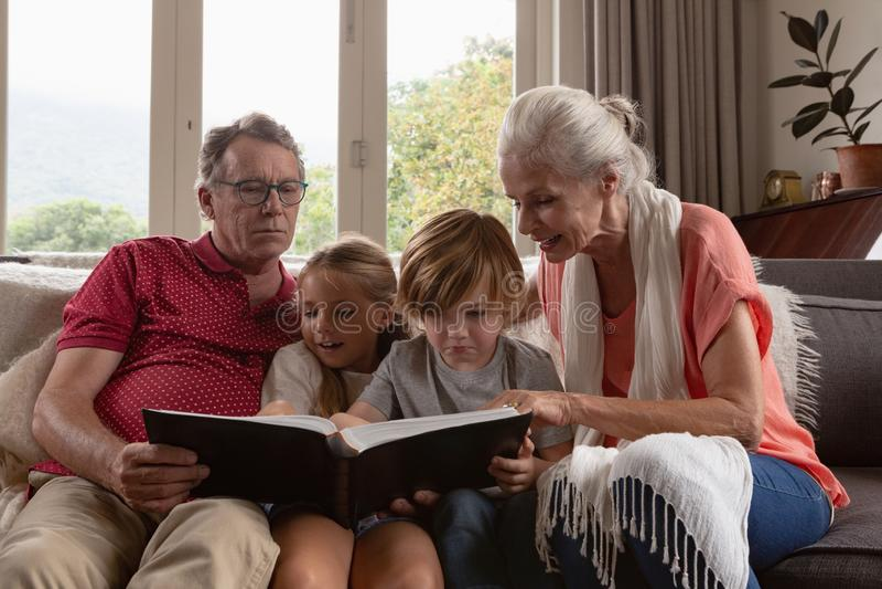 De familie die van meerdere generaties fotoalbum bekijken op bank in een comfortabel huis royalty-vrije stock foto