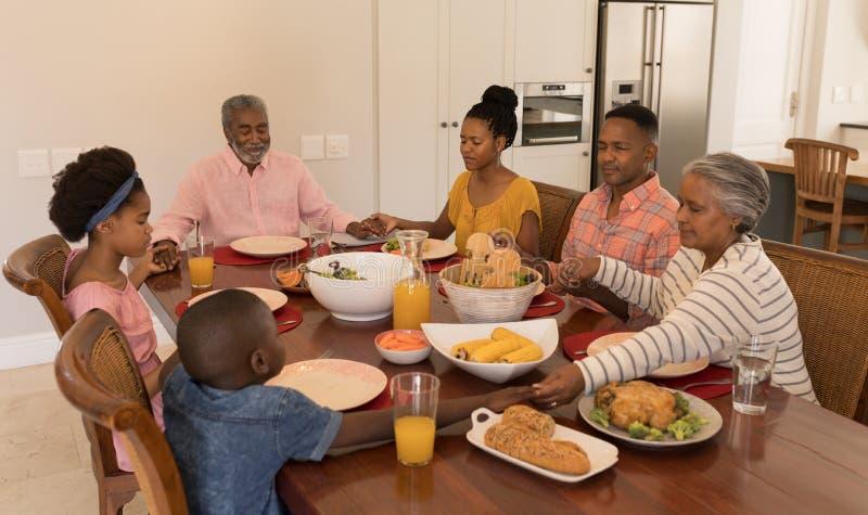De familie die van meerdere generaties samen vóór het hebben van maaltijd bidden stock foto's