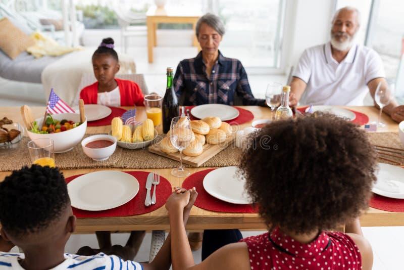 De familie die van meerdere generaties vóór het hebben van maaltijd op eettafel bidden royalty-vrije stock foto's