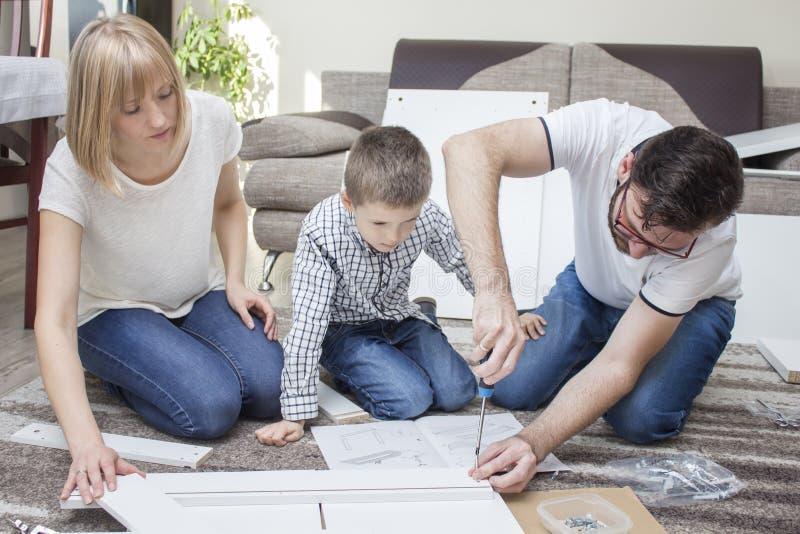 De familie draait meubilair in de woonkamer op het tapijt De vader schroefte de schroef met een schroevedraaier en de moeder en h royalty-vrije stock fotografie
