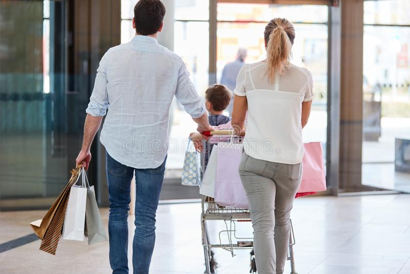 De familie duwt aankopen in boodschappenwagentje stock fotografie