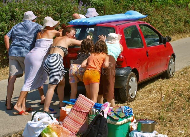 De familie duwt de auto stock afbeeldingen