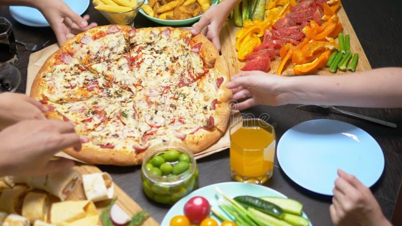 De familie eet in een comfortabel huismilieu Eigengemaakt voedsel, eigengemaakte pizza Gelukkige familie die lunch hebben die sam royalty-vrije stock foto's