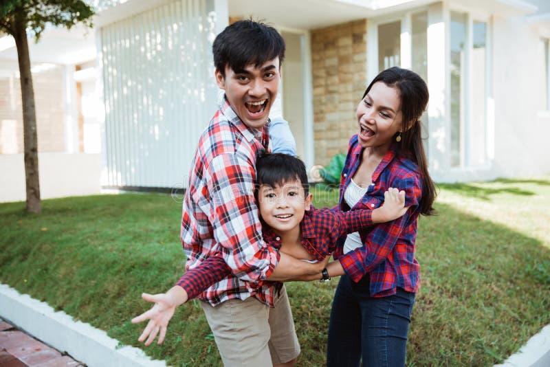 De familie en het jonge geitje genieten van speel samen voor hun huis stock foto's