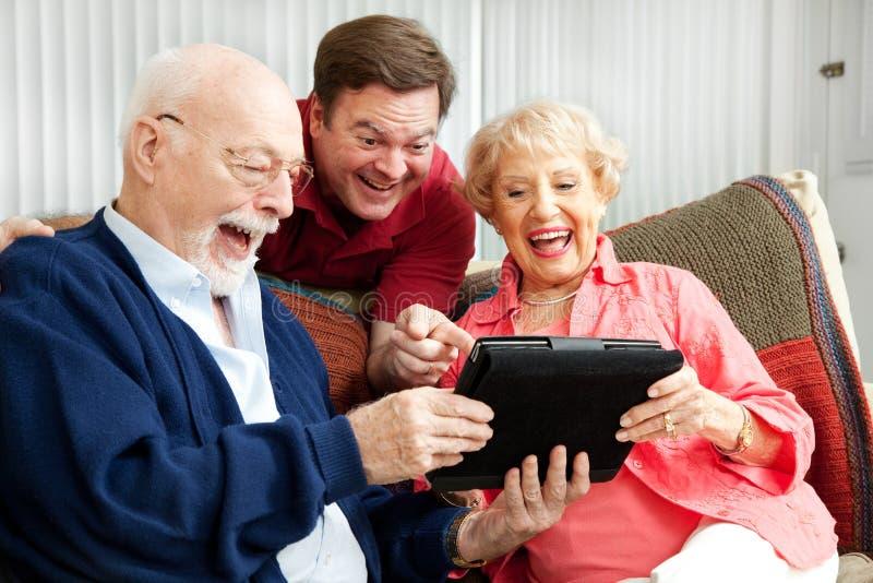 De familie gebruikt PC van de Tablet en lacht stock fotografie