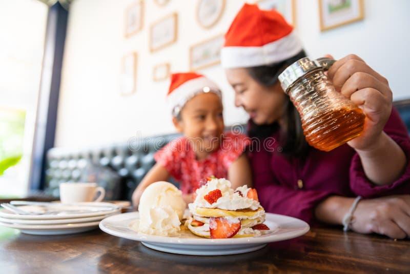 De familie geniet van etend pannekoek in Kerstavondvakantie stock foto's