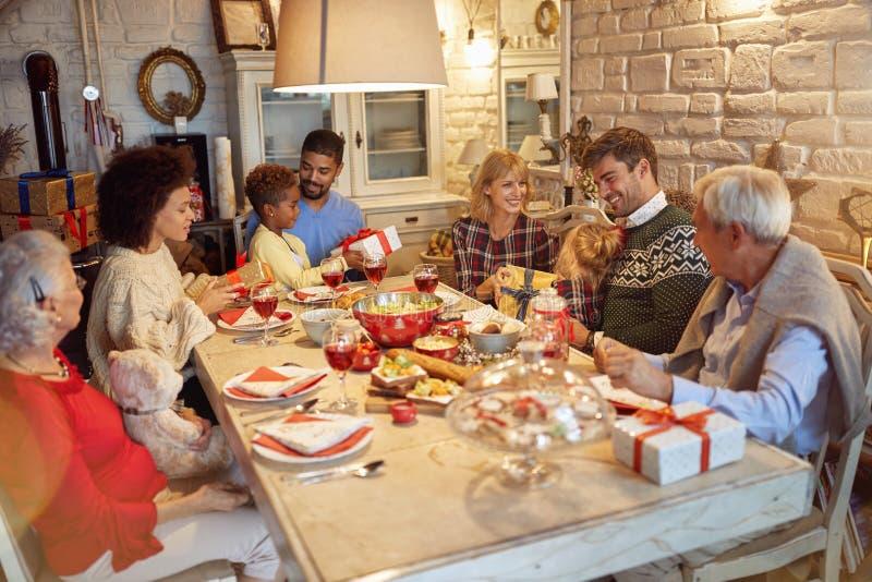 De familie geniet van op samen aanwezig Kerstmisdiner en uitwisseling royalty-vrije stock fotografie