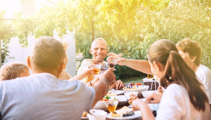 De familie heeft diner in de zomertuin stock afbeeldingen