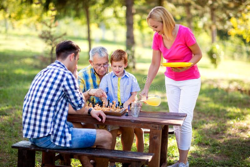 De familie heeft onderbreking in het schaak van het aardspel, stock afbeeldingen