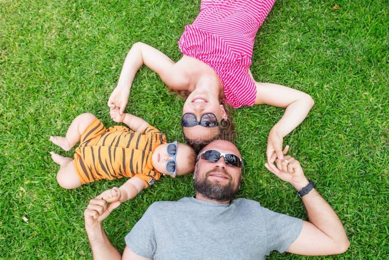 De familie heeft pret bij het groene gras dichtbij pool tijdens de zomerdag stock afbeelding